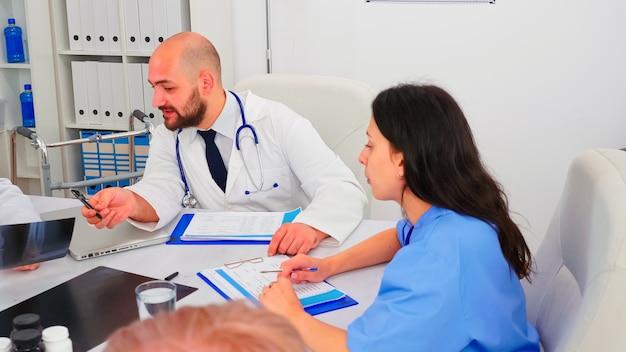病院の会議室で医師と話し、医学の専門家と説明する医療看護師。病気、専門家、専門家、コミュニケーションについて話している同僚とのクリニックセラピスト。