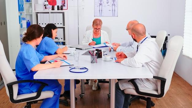病院の会議室でのヘルスケアセミナー中にクライアントのリストについてクリップボードに書き込んでいる医療看護師。病気について同僚と話しているクリニックの専門セラピスト、医学の専門家。