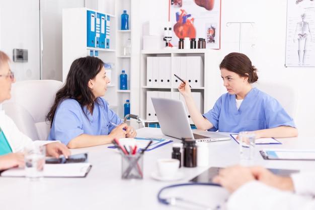 학술 의료 회의 중에 파란색 유니폼을 입고 팀워크를 하는 의료 간호사. 동료들과 함께 질병, 전문가, 전문가, 의사소통에 대해 이야기하는 클리닉 치료사.