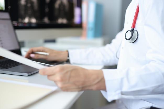 オフィスの職場の医療官はコンピューターで働いています