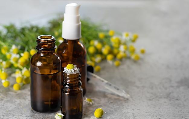 Бутылки с медицинским маслом и травы цветения ромашки на каменной поверхности.