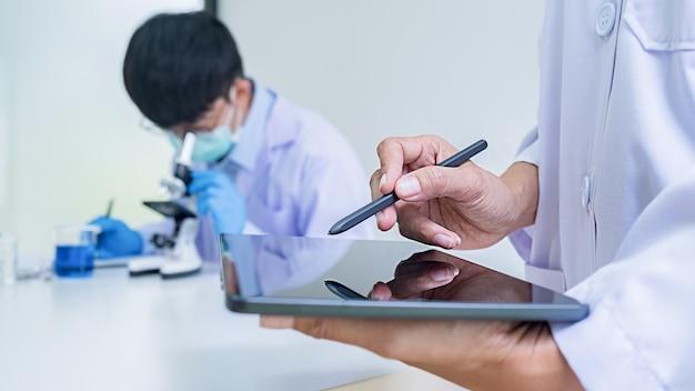 実験室で透明な溶液の試験管を見ている医学または科学の研究者または男性医師