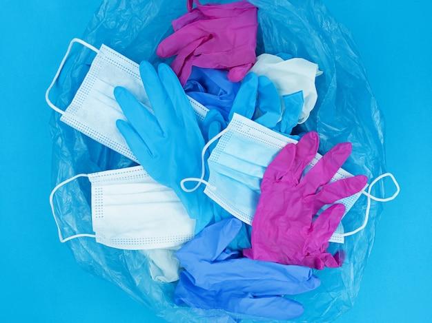 의료 유행성 코로나 바이러스 폐기물, 얼굴 마스크 및 파란색 배경에 쓰레기 봉투에 라텍스 장갑.