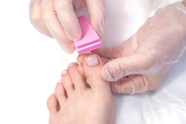 Лечебный педикюр пилочкой для ногтей. процедура пилинга ног в спа с помощью специального аппарата. клиника подиатрии подиатрия.