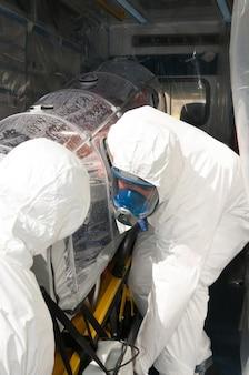 Медицинские люди с койками скорой помощи при эболе или пандемии