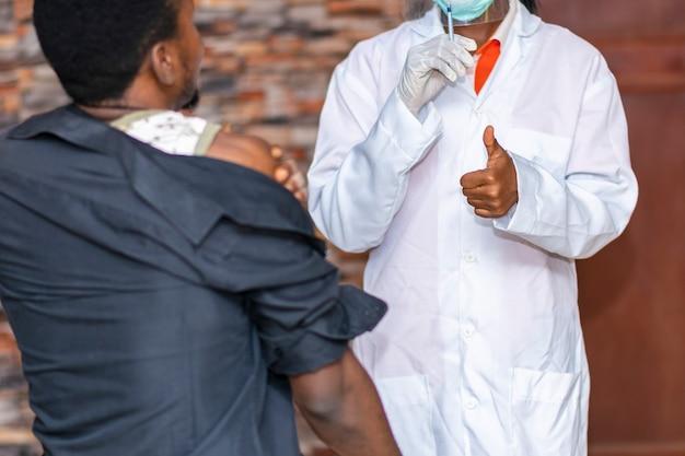 医療関係者は、ワクチン接種後に若い黒人男性に親指を立てます
