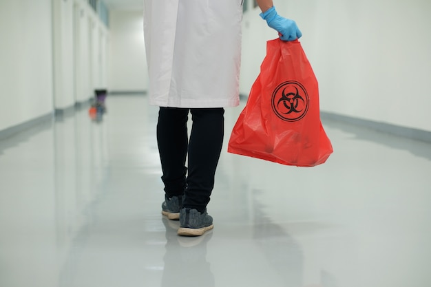 Medical personnel holding infectious waste bag.