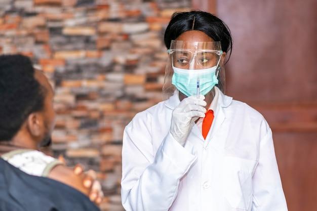 フェイスマスクとフェイスシールドを着用し、注射器を持って患者を見ている医療関係者