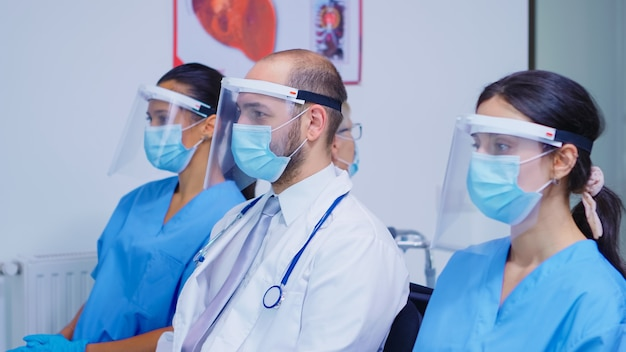 病院の待合室の椅子に座っているコロナウイルスに対するフェイスマスクとバイザーを持った医療関係者。聴診器を装着したメディック。