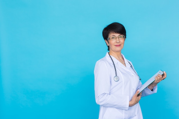 Medical physician doctor woman over blue background with copy space