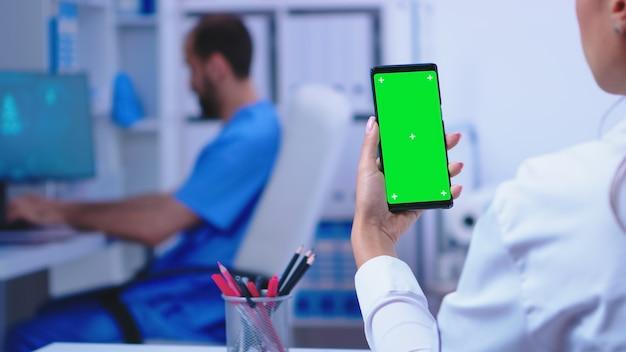 Врач держит смартфон с макетом в больничном шкафу, пока медсестра работает на компьютере. специалист в области здравоохранения в больничном шкафу с помощью смартфона с макетом.