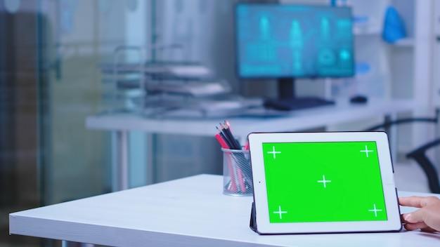 연구를 위해 병원 캐비닛에 복사 공간이 있는 태블릿 pc를 사용하여 흰색 코트를 입은 의사. 의료 클리닉의 의사는 교체 가능한 화면이 있는 태블릿 컴퓨터를 사용하여 medici를 수행하고 있습니다.
