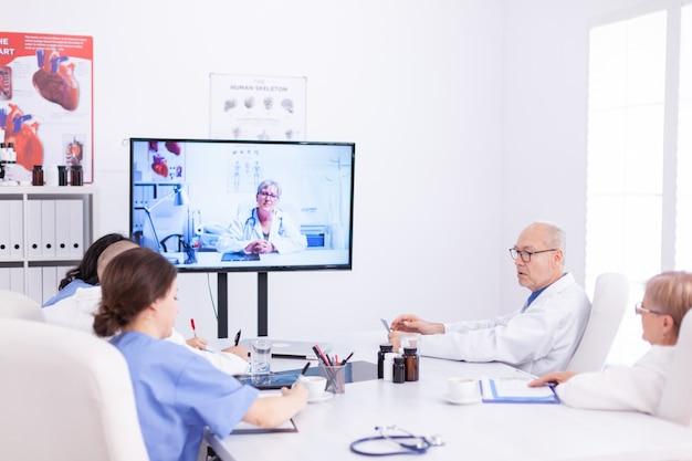 원격 회의 중에 의료 전문가와 이야기하는 의사. 전문 의사와 온라인 회의 중 인터넷을 사용하는 의료 직원.