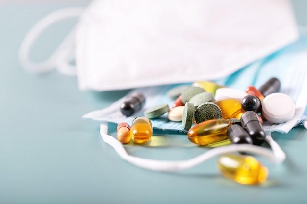 Медицинские таблетки и капсулы с медицинскими масками на синем фоне текстуры. covid-19