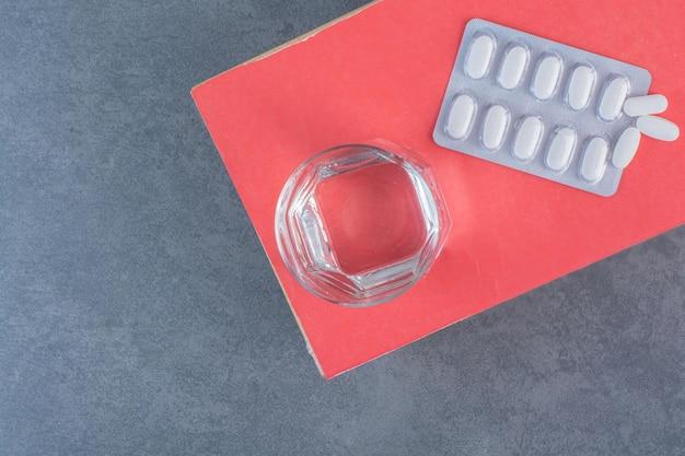 Медицинские таблетки и стакан воды на деревянном столе
