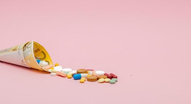 Медицинские таблетки и таблетки в банкнотах евро, деньги как символ затрат на здравоохранение