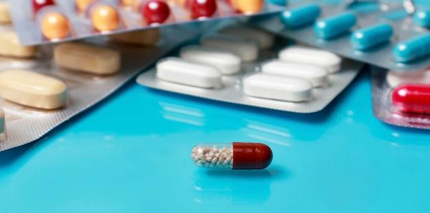 青いテーブルの上に薬が散らばっています。さまざまな色の錠剤。抗菌薬、水ぶくれの中の薬のカプセル。薬局、医学、病気、健康治療の概念。