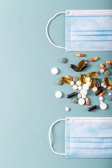 Medical pills and capsules with medical masks over blue texture background. covid-19. top view. copy space.