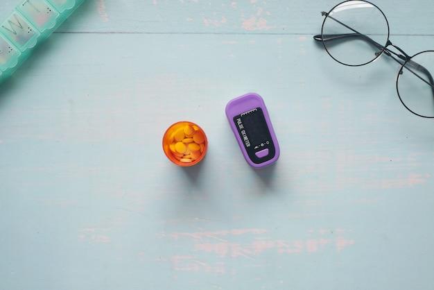 テーブルの上の医療用錠剤容器とパルスオキシメータ