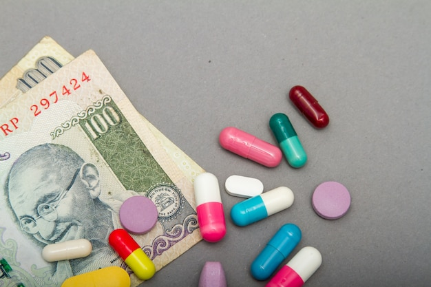Medical pills in different colors and money.