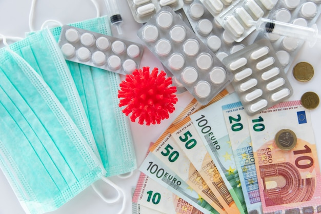Медицинские таблетки, банкноты евро, таблетки и модель коронавируса