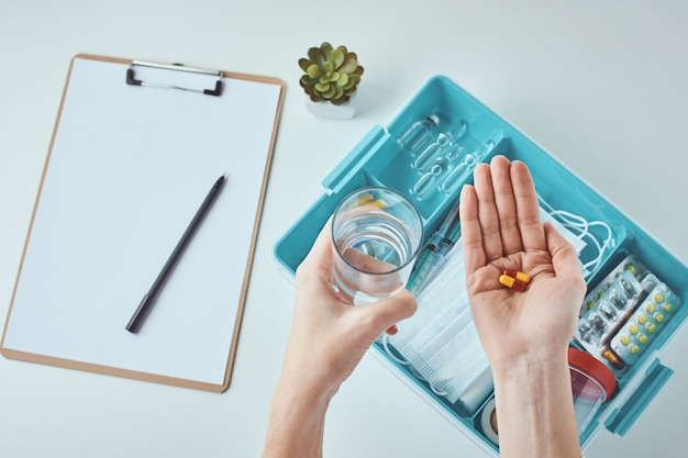 Medical pills in the hand and glass of water. healthcare and medicine concept