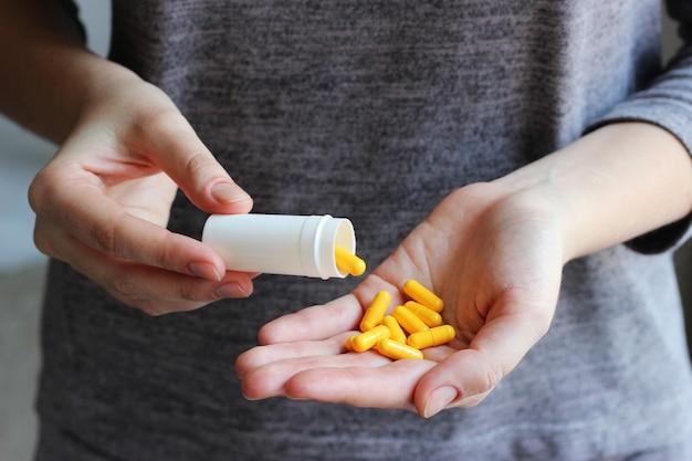 女性の手の医療用錠剤は、錠剤、ビタミン、食品添加物を服用します