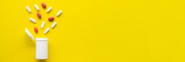 노란색 배경에 흰색 튜브에서 의료 약이 흩어져 있습니다. 모형 피임약을 엽니다. 컬러 2021 컨셉입니다. 미용 및 의학 개념입니다. 플랫 레이. 오른쪽에 텍스트를 위한 공간