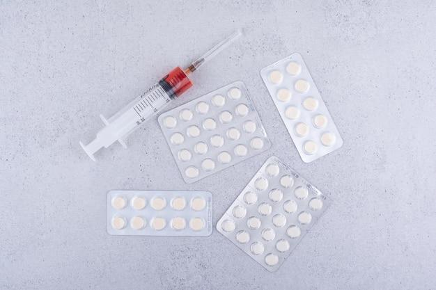Pillole mediche e siringhe su sfondo marmo. foto di alta qualità