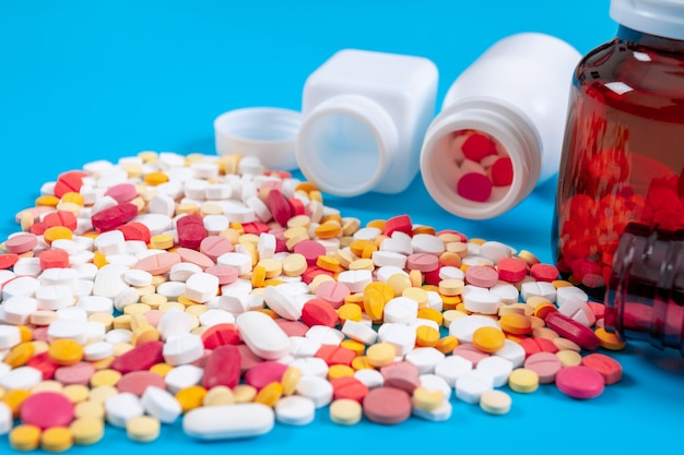 Medical pills and tablets spilling out of a drug bottle on blue background