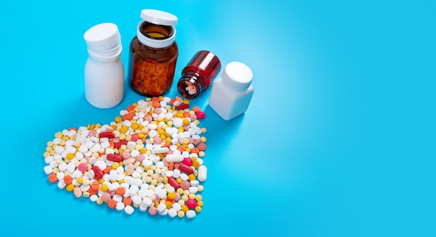 Medical pills and tablets spilling out of a drug bottle on blue table