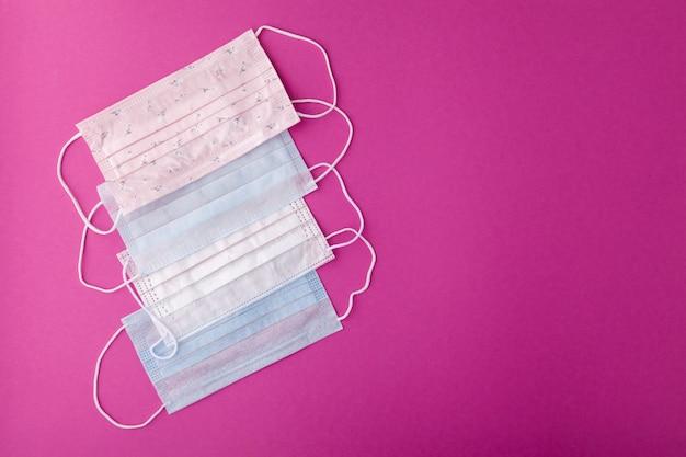 口と鼻を覆う医療用のピンク、青、白のマスク