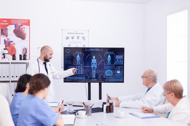 실험실 코트를 입은 동료들 앞에서 인간 시스템에 대한 프레젠테이션을 하는 의료 종사자.
