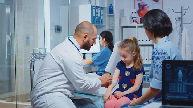 ベッドに座っている子供を負傷した腕に包帯を巻く開業医。病院のキャビネットで医療サービスのx線治療検査を提供する医療の専門医。