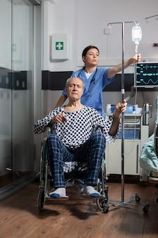 Medical practitioner preparing senior sick hospitalized man