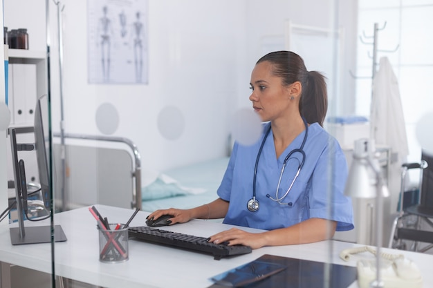 Medical practitioner using computer in hospital office. health care physician using computer in modern clinic looking at monitor, medicine, profession, scrubs.