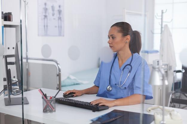 병원 사무실에서 컴퓨터를 사용하는 의사. 모니터, 약, 직업, 스크럽을 보고 있는 현대 클리닉에서 컴퓨터를 사용하는 의료 의사.