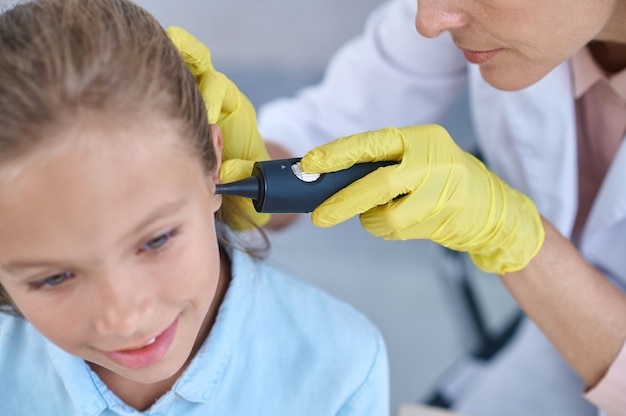 Medical procedure. focused attentive doctor in yellow gloves with special device examining ear of little smiling cute girl
