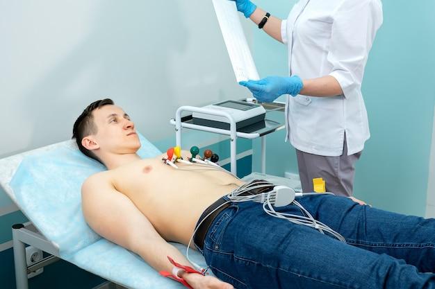 의료 전문가는 젊은 남자에게 심전도를 가져옵니다