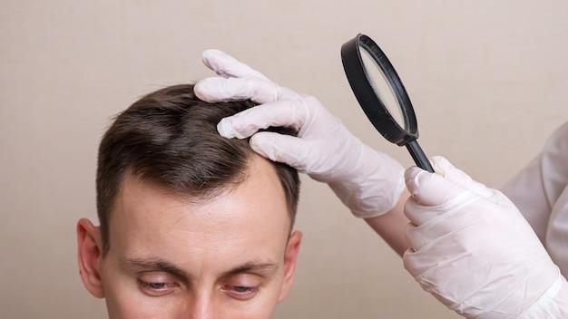 手袋と虫眼鏡を持った医療専門家が若い男の頭を調べます。