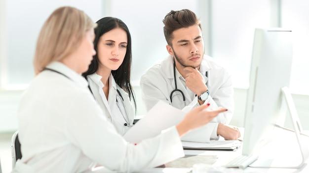 医療専門家がオフィスの机に座って何かについて話し合っている