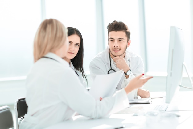 Medical professionals are discussing something sitting at the office desk . the concept of health