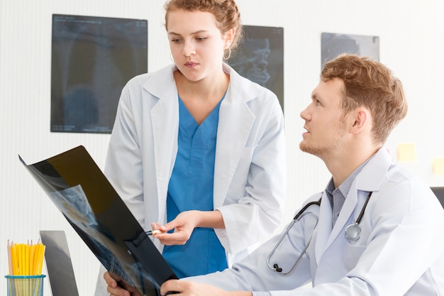 Medical professionals caucasian man holding xray and conversation about patient with young doctor woman