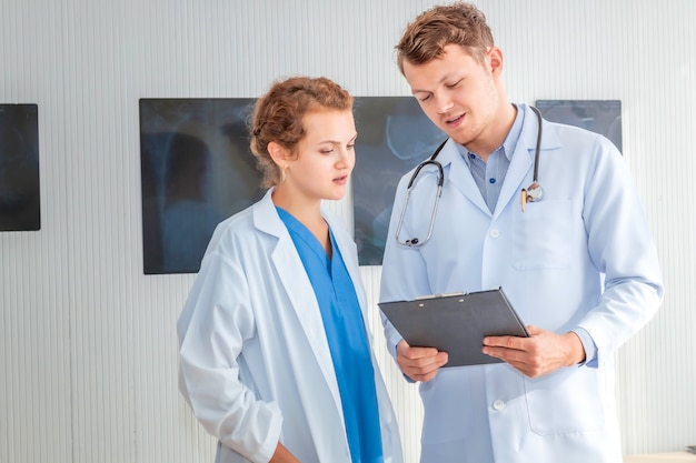 Medical professionals caucasian man holding xray and conversation about patient with young doctor woman.