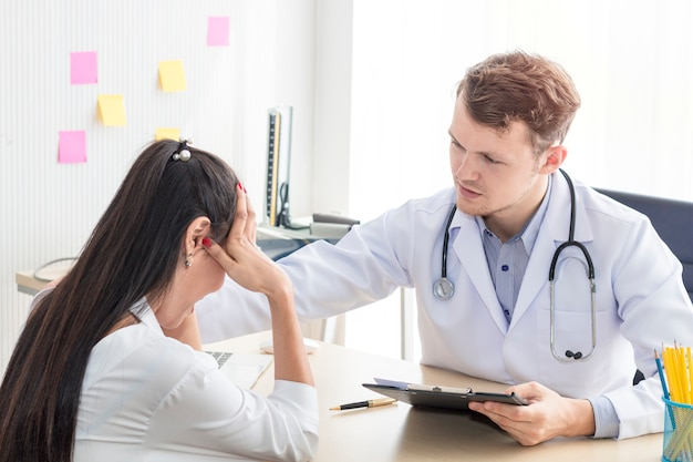 Medical professionals man reassuring and talking with young woman stress patient.