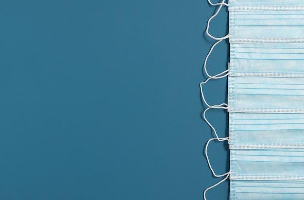 青い背景の医療保護フェイスマスク。コピースペースを持つ最小限の抽象的なコロナウイルスの背景。