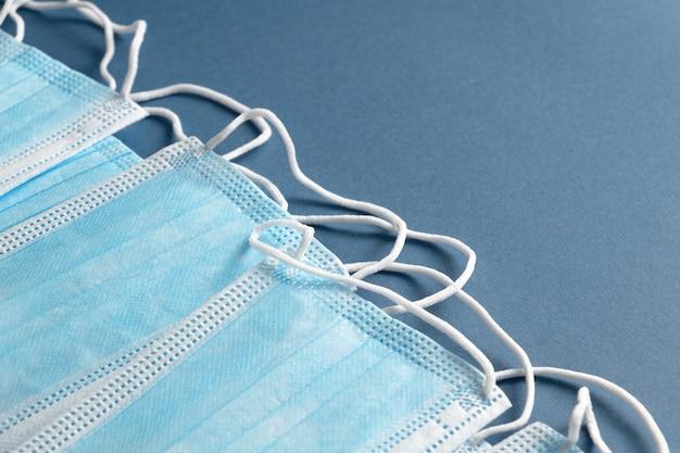 青い背景の医療保護フェイスマスク。最小限の抽象的なコロナウイルスの背景
