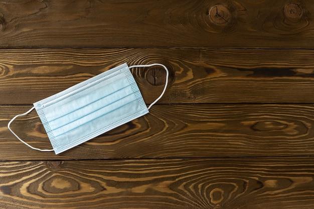 木製の背景に医療保護、青いフェイスマスク