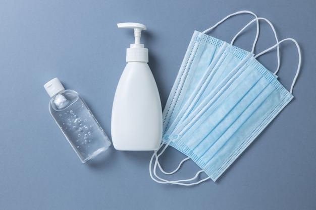 Медицинские защитные, синие маски для лица, дезинфицирующий гель, жидкое мыло для рук на серой поверхности, крупный план, ровно, минимальный. концепция гигиены, средства защиты, предотвращение распространения вирусных инфекций.