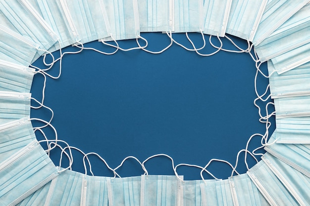 Медицинские защитные маски для лица, выложенные по кругу на синем фоне с копией пространства. плоская планировка.